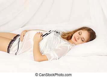 Young pregnant woman at home sleeping on the bed in bedroom