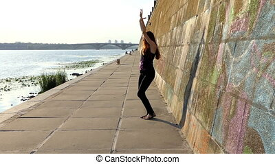 Young Pregnant Woman Dances Disco on a Riverbank With a High Wall in Slo-Mo