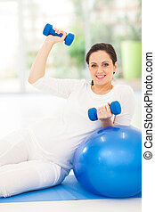 young pregnant woman doing fitness exercise