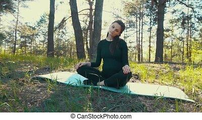 young pregnant woman doing yoga outside.