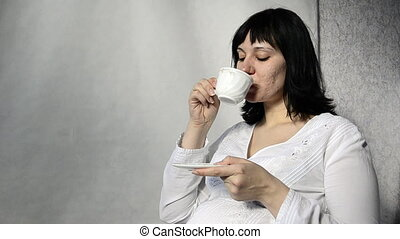 Young pregnant woman drinking tea