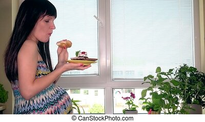 Young pregnant woman eating tasty cake sitting near window at home