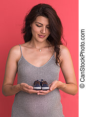 pregnant woman holding a tiny baby shoes