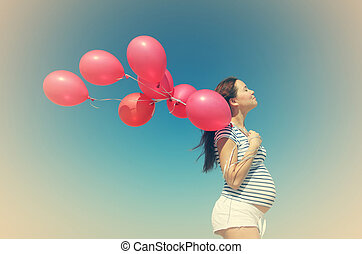 Young pregnant woman holding red balloons. Photo in old...