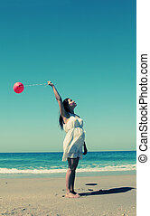 young pregnant woman holding red balloons