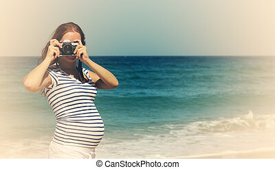 Young pregnant woman holding vintage camera. Photo in old color image style.