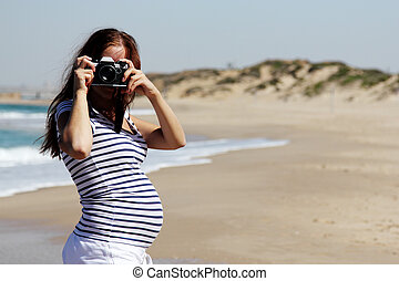 Young pregnant woman holding vintage camera