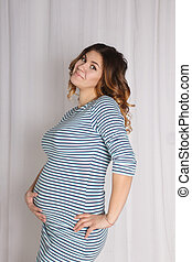 young pregnant woman in striped dress posing near white curtains in studio, hand lies on belly
