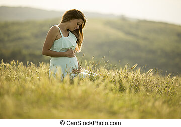 Young pregnant woman in the field