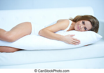 Young pregnant woman laying on sofa - Young pregnant woman...