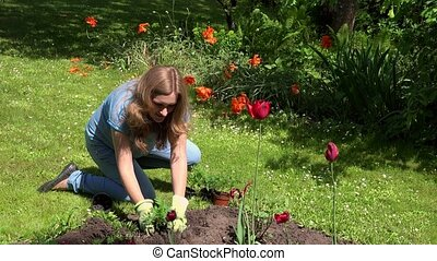 young pregnant woman planting flowers in garden