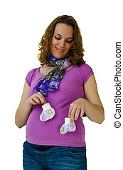 Young pregnant woman playing with baby socks