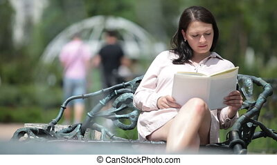 Young pregnant woman relaxing on a bench in city park reading book