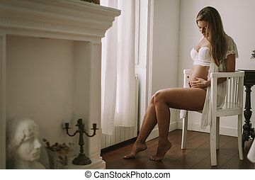 Young pregnant woman sitting in the chair