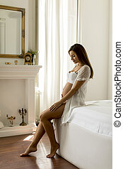 Young pregnant woman sitting on the bed