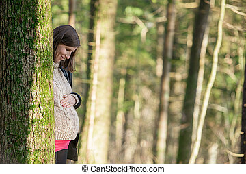 Young pregnant woman standing behind a tree