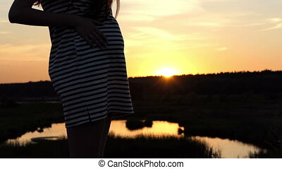 Young pregnant woman stands on a lake bank at sunset in slo-mo