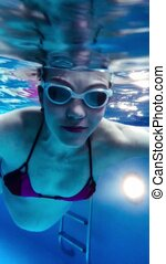 Young pregnant woman swimming underwater