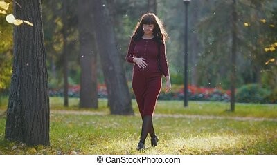 Young pregnant woman walking at autumn park among golden...
