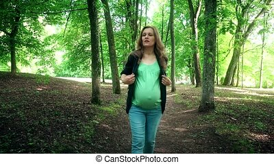 Young pregnant woman walking at summer park among tree alley