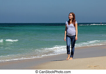 Young pregnant woman walking at the beach