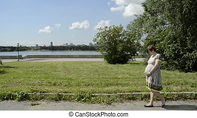 Young pregnant woman walking