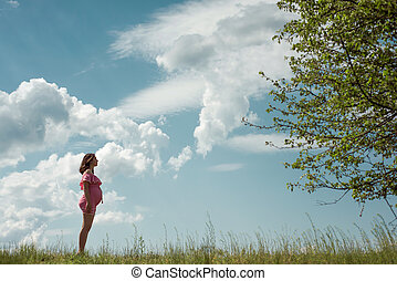 young pregnant woman wearing pink dress standing against sky with clouds in sunny day