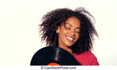 Young pretty african american woman in red top enjoying and dancing with vinyl records at white background. Modern trendy black girl with afro hairstyle.