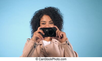 Young pretty african woman in pink jacket takes pictures...