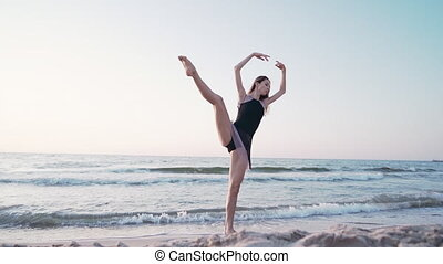 Young pretty ballerina in black dress dancing ballet on sea or ocean sandy beach in morning light. Concept of stretching, art, nature beauty