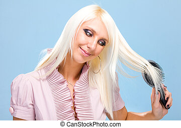 blond woman combing her beautiful long hair