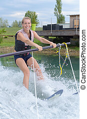 young pretty blond woman learning to ride a wakeboard