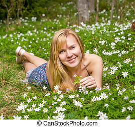 Young pretty blond woman on a meadow flowers