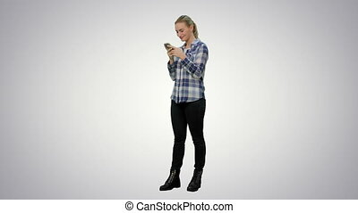 Young pretty blond woman typing on smartphone and smiling on...
