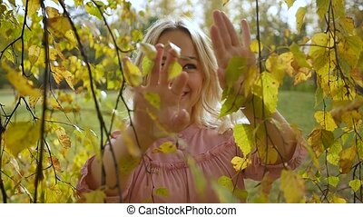 Young pretty blonde against the backdrop of an autumn park with evening light. Slow motion