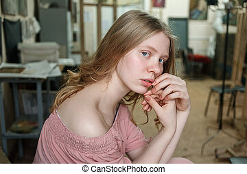 Young pretty blonde girl with blue eyes in pink dress sits in workshop, holding hands near face and looking into camera
