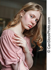 Young pretty blonde girl with blue eyes in pink dress sitting in old art studio, tilting her head and looking into camera