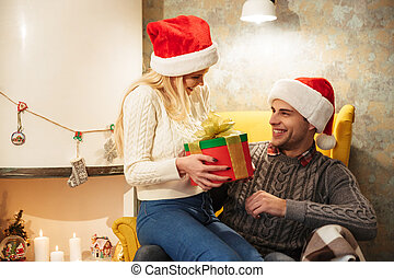 Young pretty blonde woman in Santa's hat giving present to her husband while sitting in chair at home