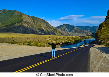 Young pretty blonde woman on a black asphalt road with yellow markings and sand on the roadside with his arms outstretched behind a picturesque landscape of Altai moumtains and turquoise river Katun