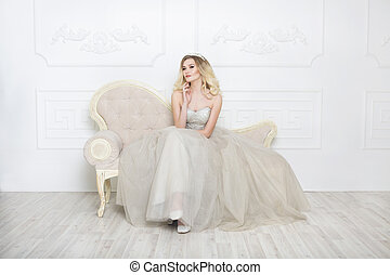 Young pretty bride wearing wedding dress indoors