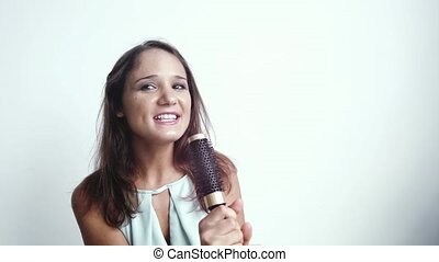 Young pretty brunette joyful woman sings song while holding a comb on a white background. slow motion. 3840x2160