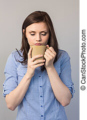 Young pretty brunette smelling coffee