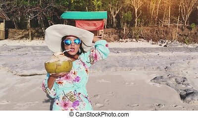Young pretty brunette smiles woman in hat and sunglasses relaxing and drinks coconut water on the ocean beach under blue sky in sunny day waving hand to the camera. Seascape view. 3840x2160
