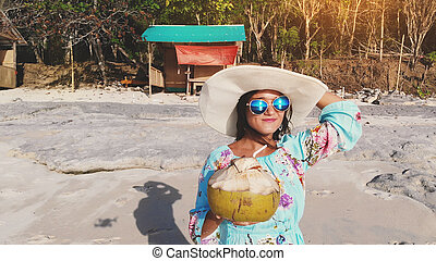 b08bc831ad6f Young pretty brunette woman holds coconut on the ocean beach under blue sky  in sunny day