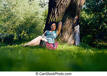 young pretty brunette woman in green park resting among grass and flowers