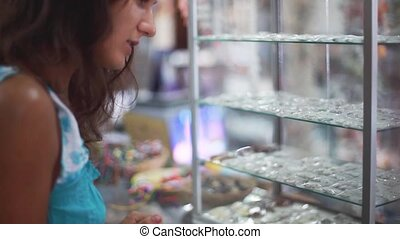 Young pretty brunette woman looking at jewellery on...