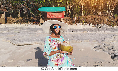 8463b57c8baa Young pretty brunette woman relaxing with coconut water on the ocean beach  under blue sky in