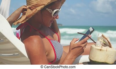 Young pretty brunette woman wearing sunglasses and hat lies on a lounger by the sea uses mobile phone.