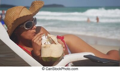 Young pretty brunette woman wearing sunglasses and hat on a lounger drinks coconut cocktail with turquoise sea background. slow motion.
