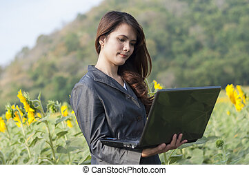 Young pretty business woman with notebook on sunflower field